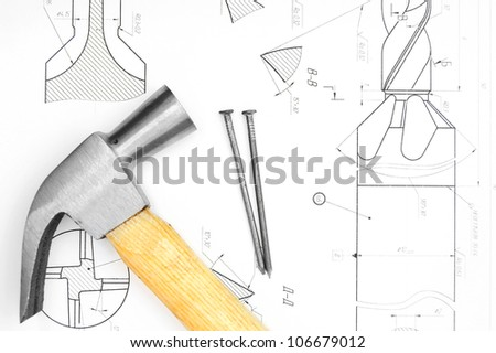 Hammer and nails on the drawing. - stock photo