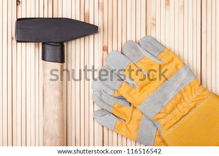 Hammer and Protective Gloves on wood. - stock photo