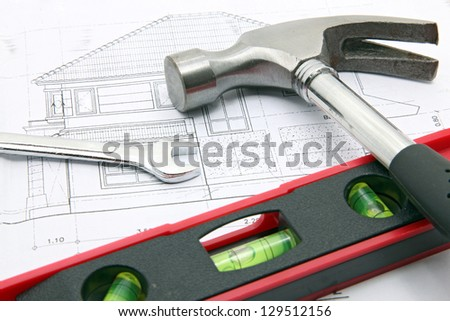 hammer and water level over a construction drawing of a house blueprint - stock photo
