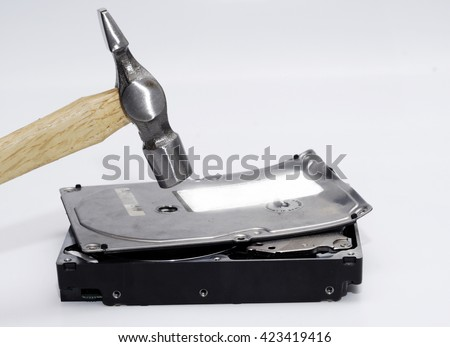 Hammer destroying hard disk drive on a white background - stock photo