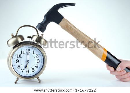 Hammer in hand and alarm clock isolated on white - stock photo
