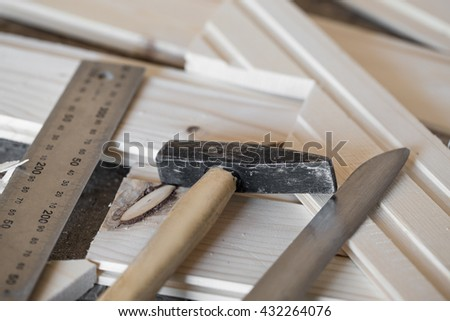 Hammer, knife, ruler and tongue and groove boards on working place, closeup - stock photo