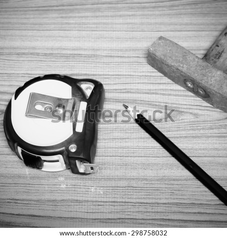 hammer measuring tape and pencil concept tools on wood background black and white color tone style - stock photo