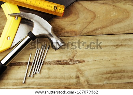 Hammer, nails, ruler and saw on wood