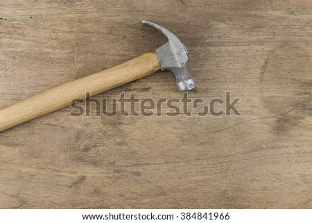Hammer on wood background