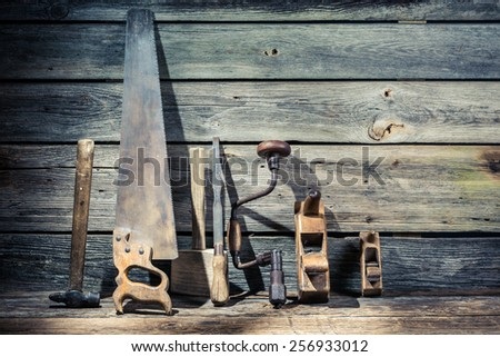 Hammer, saw and chisel in vintage workbench - stock photo