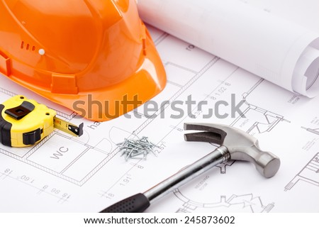 Hammer with black handle, tape measure, orange hard hat and nails on the draft - stock photo