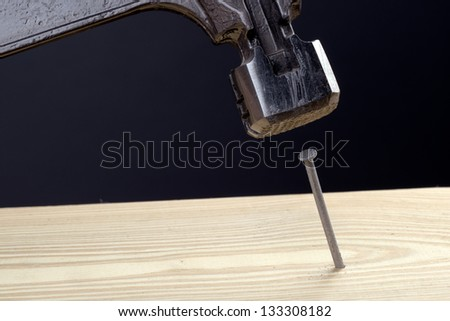 Hammering a nail into a pine board - stock photo