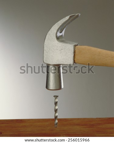 Hammering a nail on wood table. - stock photo