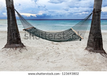 Hammock between two palm trees beside the ocean as the sun begins to set. - stock photo