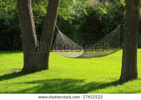 Hammock between two trees with green grass. Summertime at it's best. - stock photo