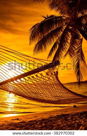 Hammock on a palm tree during beautiful sunset on tropical Fiji Islands - stock photo