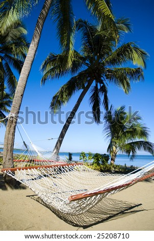 Hammock on a tropical sandy beach with palm trees.  Holiday, relaxation and rest. - stock photo