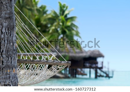 Hammock on tropical pacific ocean Island with reef bungalows in the background. - stock photo