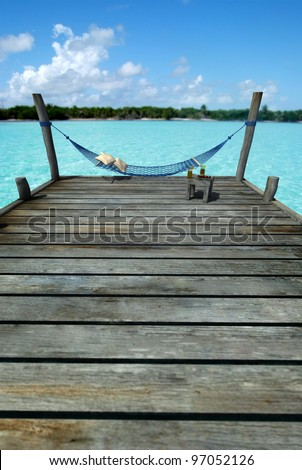 Hammock swinging in a pier by a tropical landscape, with a side table laden with fruits and refreshments - stock photo