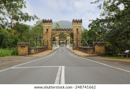 Hampden Bridge in the Kangaroo Valley is made of local sandstone with four medievil castle like turrets,  is the oldest surviving suspension bridge carrying traffic in Australia - stock photo