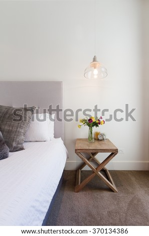 Hamptons styled bedside table with hanging pendant light in luxury home interior - stock photo