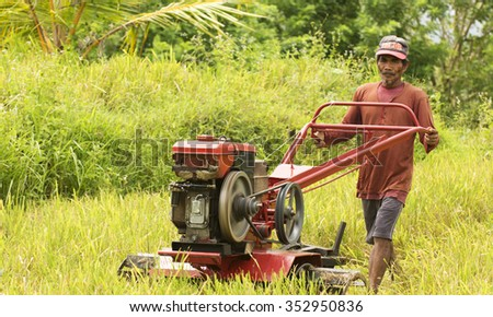 HAMTIC - PHILIPPINES - OCTOBER 18TH: Filipino man plowing hes new harvested rice field in the Philippines - stock photo