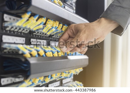 hand a hacker with network cables connected to servers in a data - stock photo