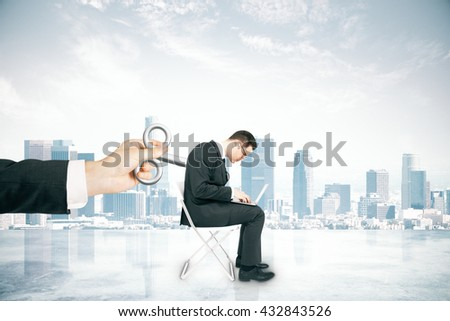 Hand activating businessman with a wind-up key on his back on foggy city background. Concept of control