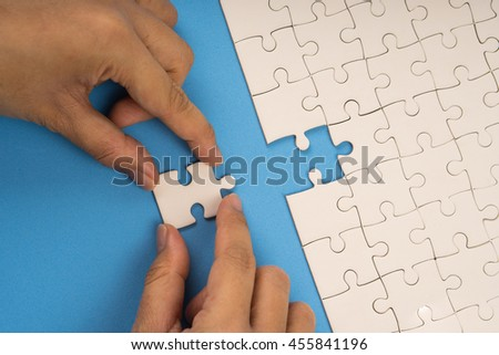 hand add last jigsaw puzzle connection, blue background - stock photo