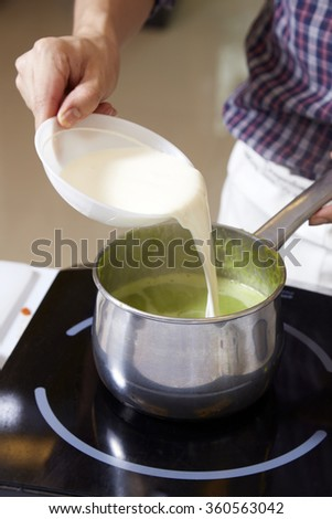 Hand adding milk cream into pot of pea soup