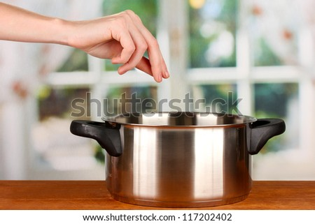 Hand adding salt on bright background - stock photo