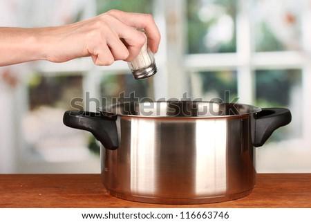 Hand adding salt using  salt shaker on bright background - stock photo