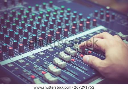 Hand adjusting audio mixer - stock photo