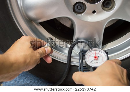 hand and car wheel add air pressure - stock photo