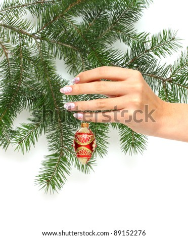 Hand and christmas decoration beside christmas tree