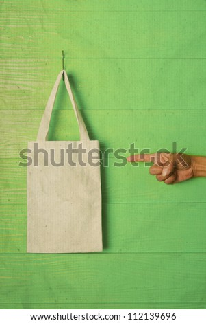 hand and finger pointing to clothes bag on green background concept for save nature reused bag - stock photo