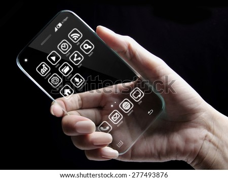 Hand and futuristic transparent smartphone isolated on black background. The most promising technologies in the mobile market is flexible and transparent displays.  - stock photo