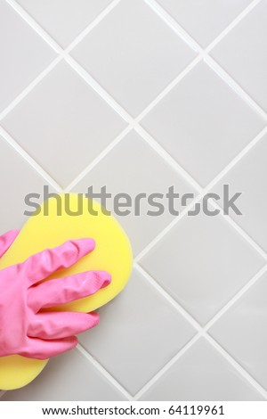Hand and glove cleaning the bathroom tiles. - stock photo