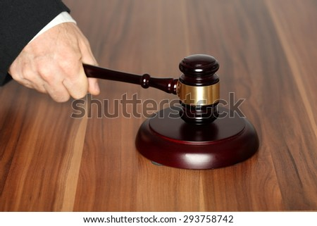 hand and hammer on table, law symbol - stock photo