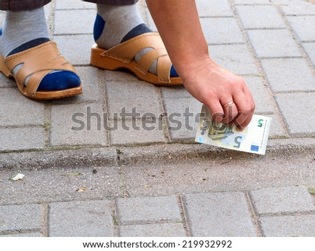 Hand and lost banknote on footpath close up - stock photo