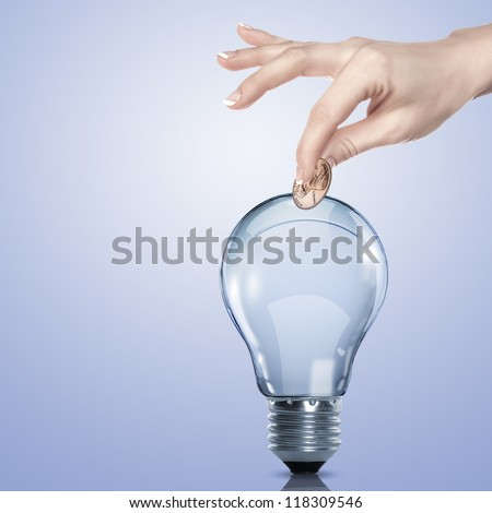Hand and money inside an electric light bulb - stock photo