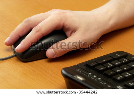 Hand and mouse with an office desk as a background
