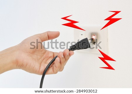Hand and Plug Electricity shock - stock photo