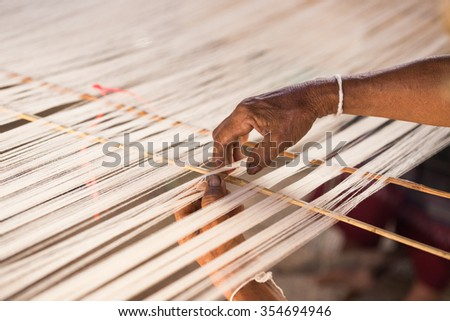 hand and white silk thread in sewing or weaving machine,texture,background