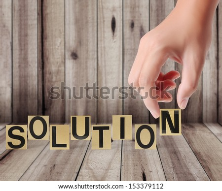 Hand and word solution on a wood background  - stock photo