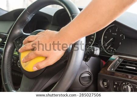 Hand applying polish in the car - stock photo