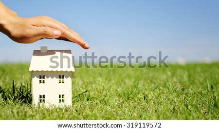 Hand as a protecting roof over a little house - stock photo