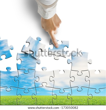 Hand assembling puzzle with beautiful landscape isolated in white background - stock photo