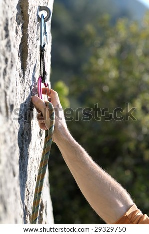 hand attaching karabiner to a rock