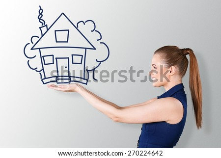 Hand. Beautiful young lady holding a huge drawn house - stock photo