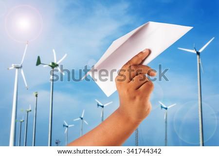 hand boy play paper plane on wind turbine background - stock photo