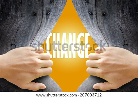 "Hand breaking a wooden wall found the word ""CHANGE"" on the bright yellow background. - stock photo"