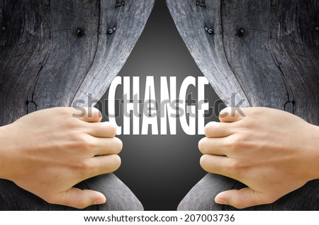 "Hand breaking a wooden wall found the word ""CHANGE"" on the magic gray background. - stock photo"