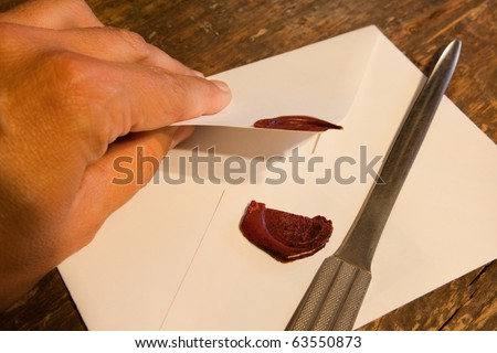 Hand breaking the wax seal of a confidential envelope - stock photo